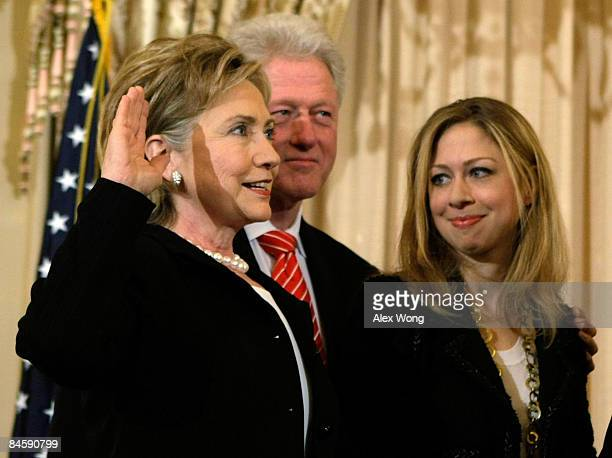S Secretary of State Hillary Clinton is sworn in as her husband former President Bill Clinton and her daughter Chelsea look on during a ceremonial...