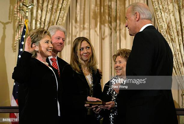 S Secretary of State Hillary Clinton is sworn in by Vice President Joseph Biden as her husband former President Bill Clinton her daughter Chelsea and...