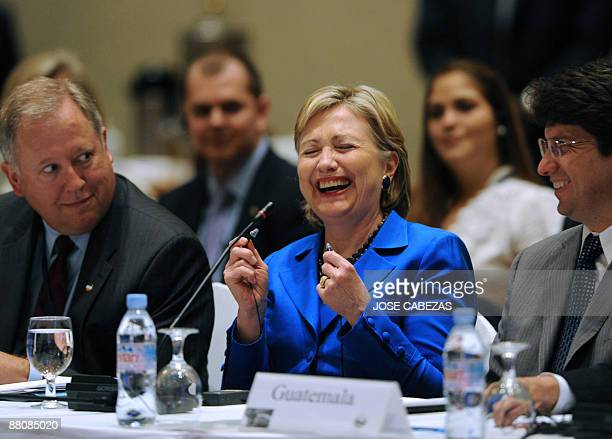 US Secretary of State Hillary Clinton laughs as she participates in the Pathways to prosperity meeting in San Salvador next to US Deputy Secretary of...