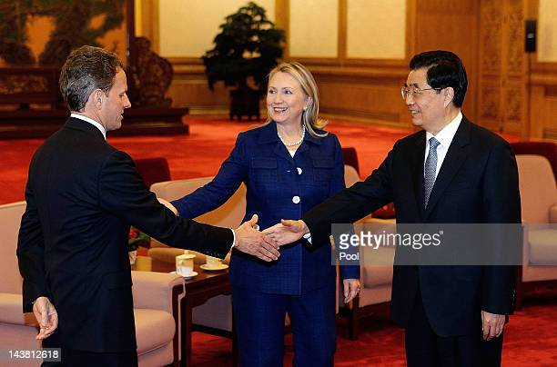 S Secretary of State Hillary Clinton looks on as Chinese President Hu Jintao shakes hands with US Treasury Secretary Timothy Geithner during a...