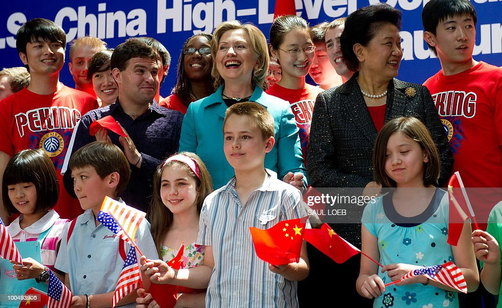 US Secretary of State Hillary Clinton (top C) poses for photos alongside Chinese State Councilor Liu Yandong (2nd R) and American and Chinese students after watching a performance at the National Center for the Performing Arts in Beijing on May 25, 2010. The United States and China were wrapping up strategic talks aimed at smoothing out differences on currency and trade issues, as Washington presses Beijing to get tough on North Korea. AFP PHOTO / POOL / Saul LOEB