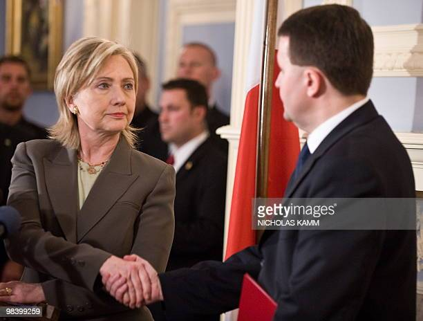 US Secretary of State Hillary Clinton shakes hands with Polish Ambassador to the US Robert Kupiecki after signing the condolence book at the Polish...