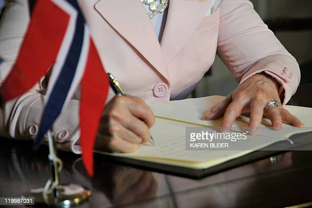 US Secretary of State Hillary Clinton signs a book of condolence at the Norwegian Embassy on July 28 2011 in Washington DC Clinton made the visit to...