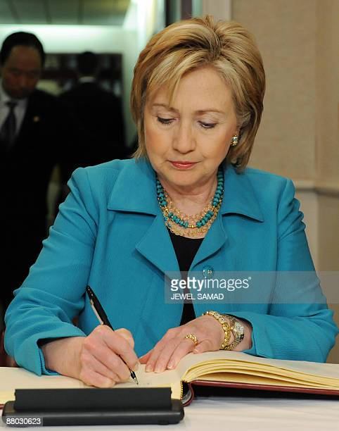 US Secretary of State Hillary Clinton signs a condolence book for late former South Korean president Roh MooHyun at the South Korean embassy in...