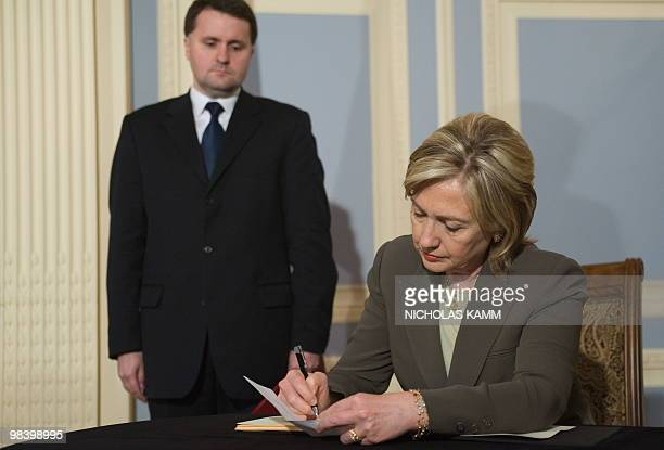 US Secretary of State Hillary Clinton signs the condolence book at the Polish Embassy in Washington on April 11 2010 before Ambassador Robert...