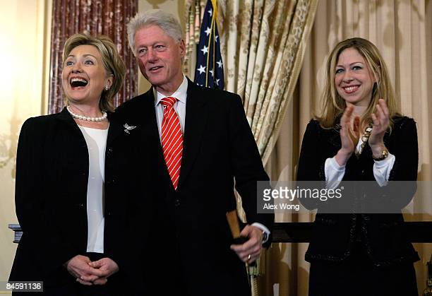 S Secretary of State Hillary Clinton smiles as her husband former President Bill Clinton and daughter Chelsea look on during a ceremonial swearingin...