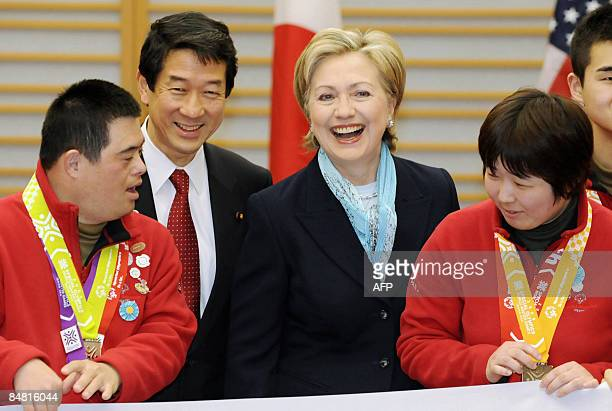 Secretary of State Hillary Clinton smiles as she poses for photos with athletes of the Special Olympics World Winter Games upon her arrival at Haneda...