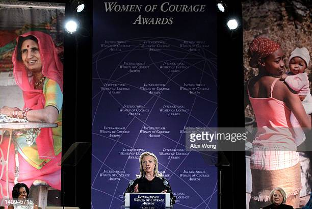 S Secretary of State Hillary Clinton speaks as first lady Michelle Obama listens during the presentation ceremony of the International Women of...