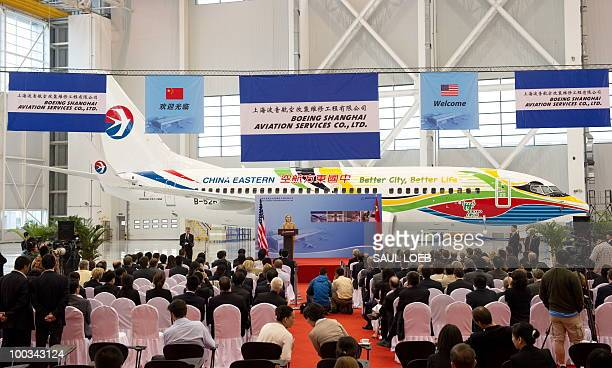 US Secretary of State Hillary Clinton speaks on commercial development in front of a China Eastern Boeing 737 at the Boeing Maintenance Facility at...