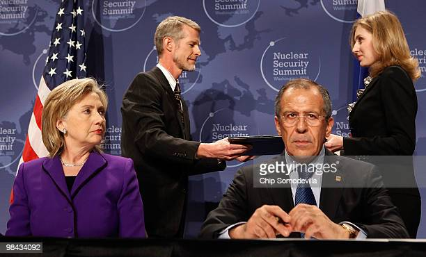 Secretary of State Hillary Rodham Clinton and Russian Foreign Minister Sergey Lavrov wait as aides exchange signed copies of an agreement on...