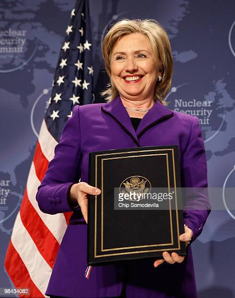 Secretary of State Hillary Rodham Clinton holds her copy of an agreement on eliminating excess weapon-grade plutonium from her country's and the...