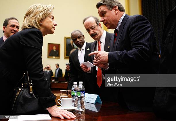S Secretary of State Hillary Rodham Clinton talks to Rep Chris Smith as Rep Eliot Engel and Rep David Scott look on after a hearing before the House...