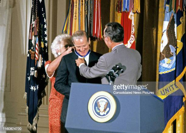 US Secretary of State James A Baker III smiles as American First Lady Barbara Bush and US President George HW Bush fasten the Presidential Medal of...