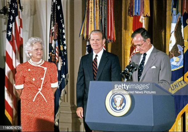 US Secretary of State James A Baker III stands between First Lady Barbara Bush and US President George HW Bush during his Presidential Medal of...
