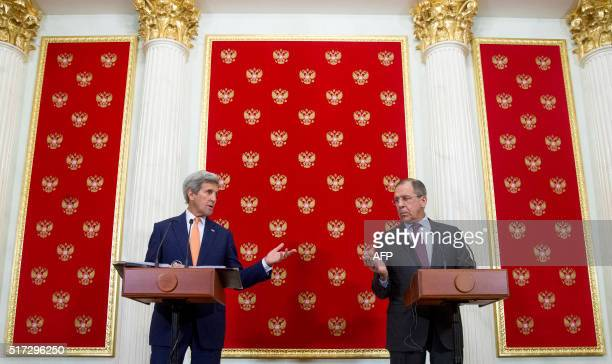 US Secretary of State John Kerry and Russian Foreign Minister Sergey Lavrov gesture towards each other to give a chance to answer a question from a...