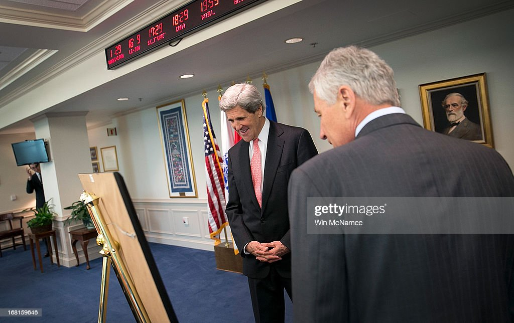 U.S. Secretary of State John Kerry (R) and U.S. Secretary of Defense Chuck Hagel (L) discuss a gift Hagel gave to Kerry prior to a meeting in Hagel's office at the Pentagon May 6, 2013 in Arlington, Virginia. The print, a copy of a painting titled, 'Showing the Flag in Ca Mau (PT-71)', depicts a scene of a Naval Patrol Craft Boat of the type that Kerry commanded during the war in Vietnam. Kerry and Hagel met for a working lunch to discuss a range of national security issues.