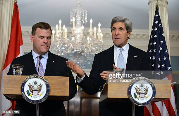 Secretary of State John Kerry answers a question as Canadian Foreign Minister John Baird looks on during a press briefing following their meeting at...