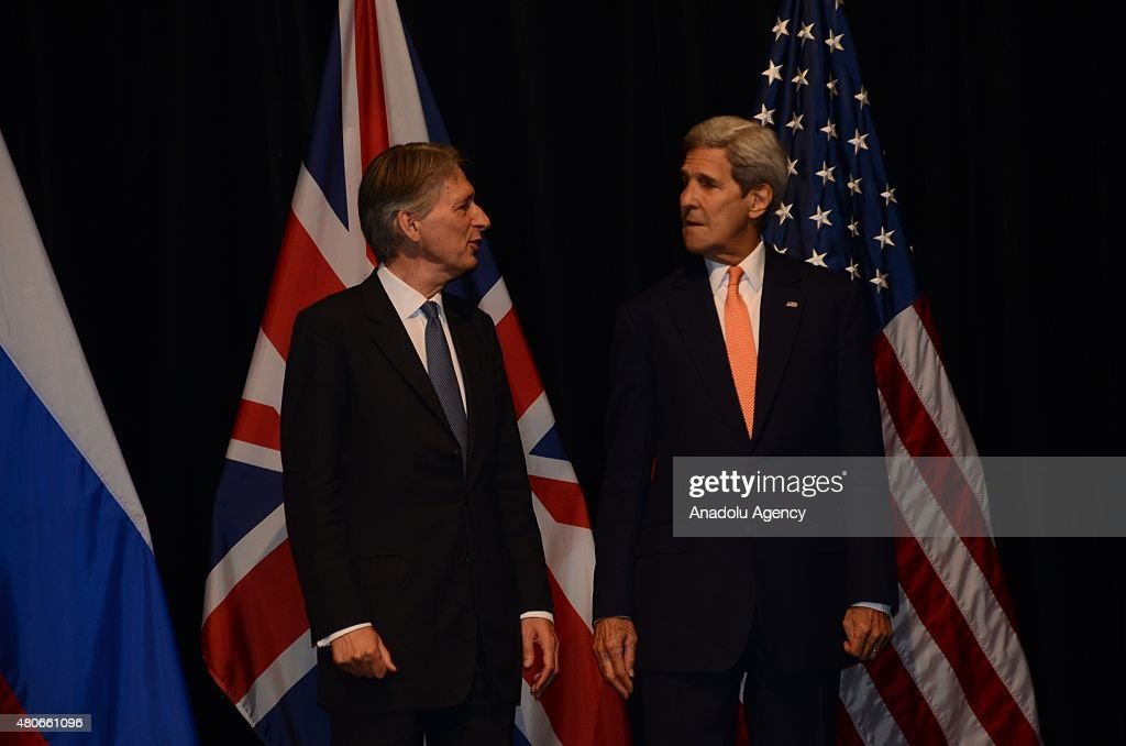 US Secretary of State John Kerry (R), British Foreign Secretary Philip Hammond (L), Iran's Foreign Minister Javad Zarif (not seen), High Representative of the European Union for Foreign Affairs and Security Policy Federica Mogherini (not seen), German Minister for Foreign Affairs Frank-Walter Steinmeier (not seen), French Foreign Minister Laurent Fabius (not seen) and China's Foreign Minister Wang Yi (not seen) poses for a family shoot after they concluded the Iran nuclear talk meetings with a deal in Vienna, Austria on July 14, 2015.
