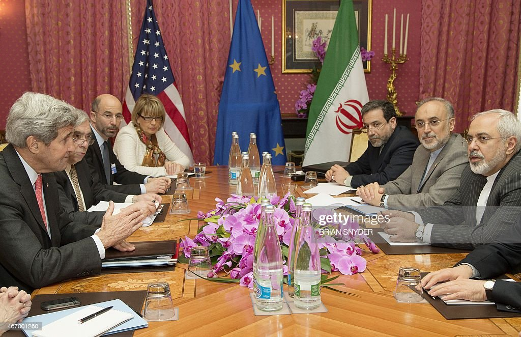 US Secretary of State John Kerry (L) expresses his condolences over the death the of the mother of Iranian President Hassan Rouhani (unseen) before a negotiation session with Iran's Foreign Minister Javad Zarif (R) over Iran's nuclear program in Lausanne March 20, 2015, as European Union Political Director Helga Schmid (4-L) looks on. Marathon talks towards an Iran nuclear deal picked up pace as US President Barack Obama appealed to Tehran to seize an 'historic' opportunity and begin a 'brighter future'. AFP PHOTO / POOL /Brian Snyder