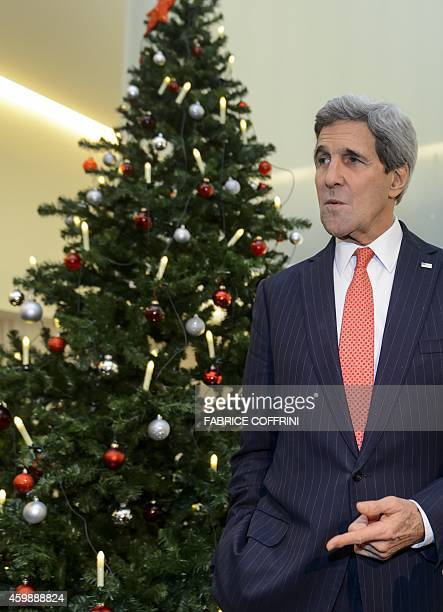 US Secretary of State John Kerry gestures as he stands next to a Christmas tree on the eve of an Organization for Security and Cooperation in Europe...