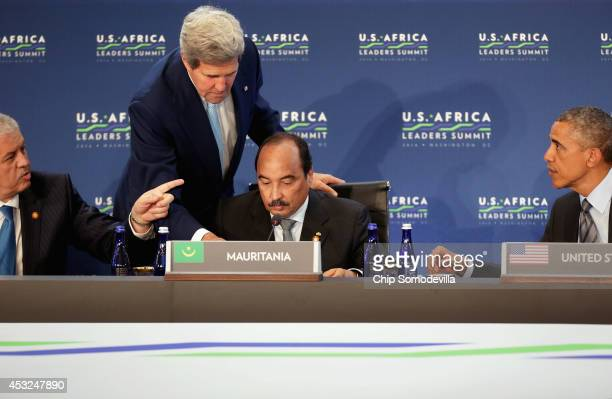 Secretary of State John Kerry helps Mauritania President Mohamed Ould Abdel Aziz on a microphone issue as U.S. President Barack Obama and Prime...