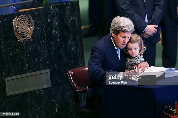 S Secretary of State John Kerry holds his two yearold grand daughter Isabel DobbsHigginson for the signing of the accord at the United Nations...