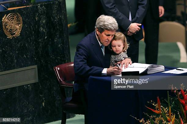 Secretary of State John Kerry holds his two year-old grand daughter Isabel Dobbs-Higginson for the signing of the accord at the United Nations...