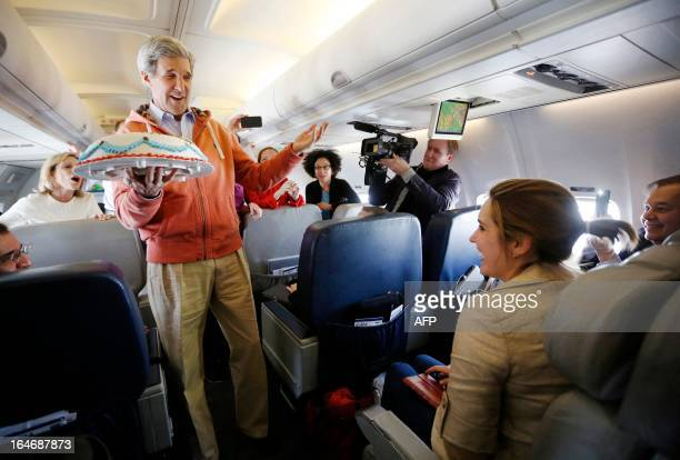 US Secretary of State John Kerry presents a birthday cake to travelling CBS correspondent Margaret Brennan on his flight from Kabul to Paris on March...
