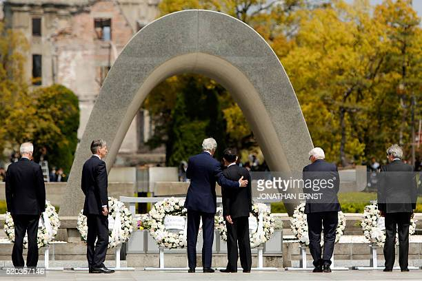 US Secretary of State John Kerry puts his arm around Japan's Foreign Minister Fumio Kishida after they and fellow G7 foreign ministers laid wreaths...