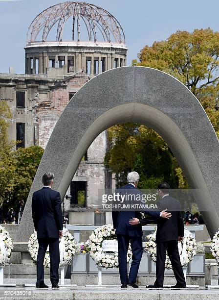 US Secretary of State John Kerry puts his arm around Japan's Foreign Minister Fumio Kishida after laying wreaths with Britain's Foreign Secretary...
