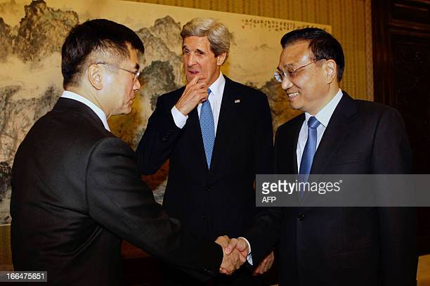 US Secretary of State John Kerry reacts as US Ambassador to China Gary Locke shakes hands with China's Premier Li Keqiang during a meeting at the...