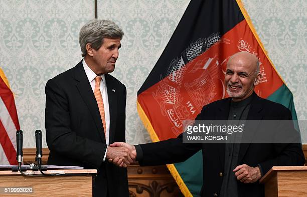 US Secretary of State John Kerry shakes hands with Afghan President Ashraf Ghani during a press conference at the Presidential Palace in Kabul on...