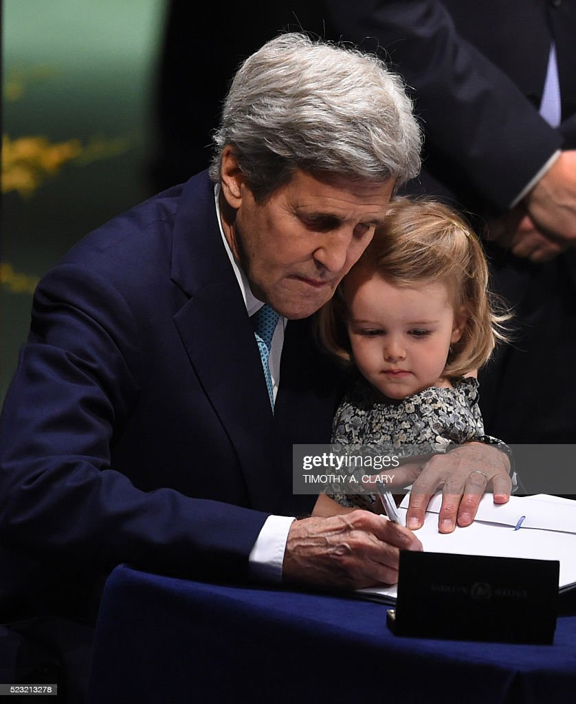US Secretary of State John Kerry signs the book holding his granddaughter, during the signature ceremony for the Paris Agreement at the United Nations General Assembly Hall on April 22, 2016 in New York. / AFP / TIMOTHY