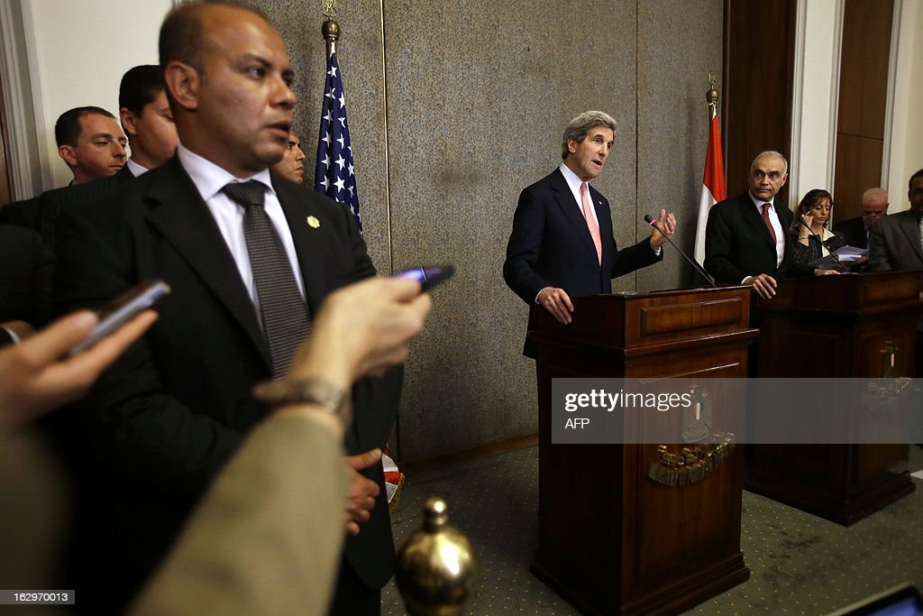 US Secretary of State John Kerry (C) speaks beside Egyptian Foreign Minister Mohammed Kamel Amr (R) while reporters and security stand by during a news conference at the Ministry of Foreign Affairs in Cairo on March 2, 2013. Kerry urged bickering Egyptian political leaders to forge a consensus to pave the way for aid that could help lift their country out of its deep economic crisis.
