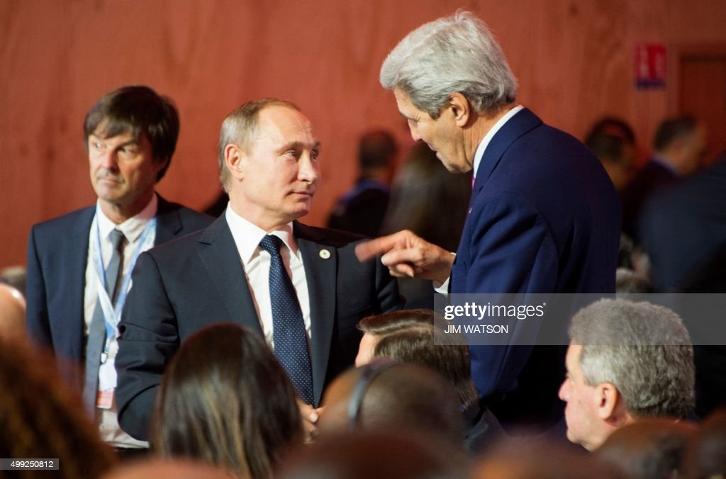 US Secretary of State John Kerry (R) speaks with Russian President Vladimir Putin (C) during the opening ceremony of the World Climate Change Conference 2015 (COP21) at Le Bourget, near Paris, on November 30, 2015. More than 150 world leaders are meeting under heightened security, for the 21st Session of the Conference of the Parties to the United Nations Framework Convention on Climate Change (COP21/CMP11), also known as 'Paris 2015' from November 30 to December 11. / AFP / JIM