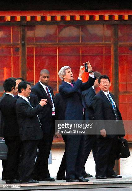 S Secretary of State John Kerry takes photographs with his mobile phone during their visit of Itsukushima Jinja Shrine on the sidelines of the G7...