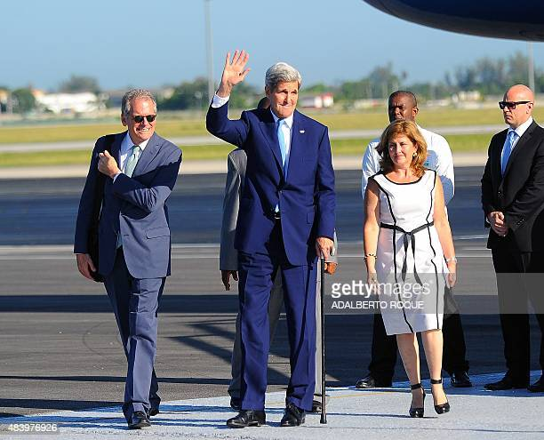 US Secretary of State John Kerry waves next to the Chief of Mission at the US Embassy in Havana Jeffrey DeLaurentis upon his arrival at Jose Marti...