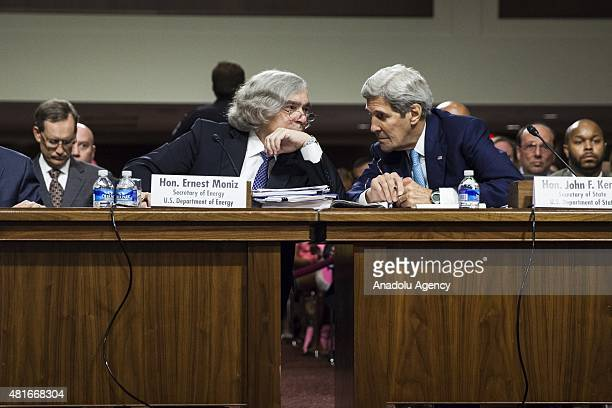 Secretary of State John Kerry whispers with Energy Secretary Ernest Moniz during a Senate Foreign Relations Committee hearing on President ObamaÕs...