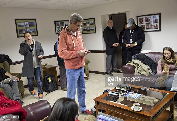Secretary of State John Kerry works on his phone during a refueling stop at Elmendorf Air Force Base in Anchorage, Alaska on February 12, 2014. Kerry...