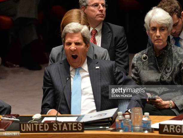 US Secretary of State John Kerry yawns as he listens to speakers in the Security Council just after the Council voted to approve a resolution that...