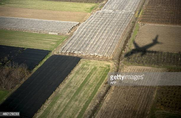 US Secretary of State John Kerry's plane casts a shadow on fields as it approaches Ben Gurion Airport on January 2 2014 in Tel Aviv Israel Kerry...