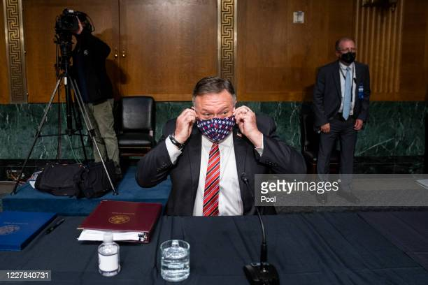 S Secretary of State Mike Pompeo adjusts his mask while preparing to testify before a Senate Foreign Relations committee hearing on the State...
