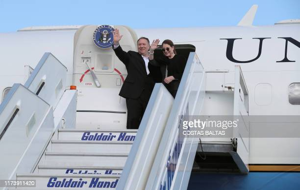 US Secretary of State Mike Pompeo and his wife Susan wave as they board their plane to depart from Eleftherios Venizelos International Airport in...
