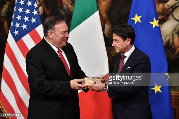 US Secretary of State Mike Pompeo hands to Italy's Prime Minister Giuseppe Conte a package of Parmesan cheese after it was handed to Pompeo by...