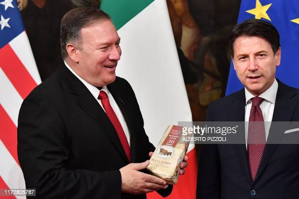US Secretary of State Mike Pompeo holds a package of Parmesan cheese as Italy's Prime Minister Giuseppe Conte reacts after the package was handed to...