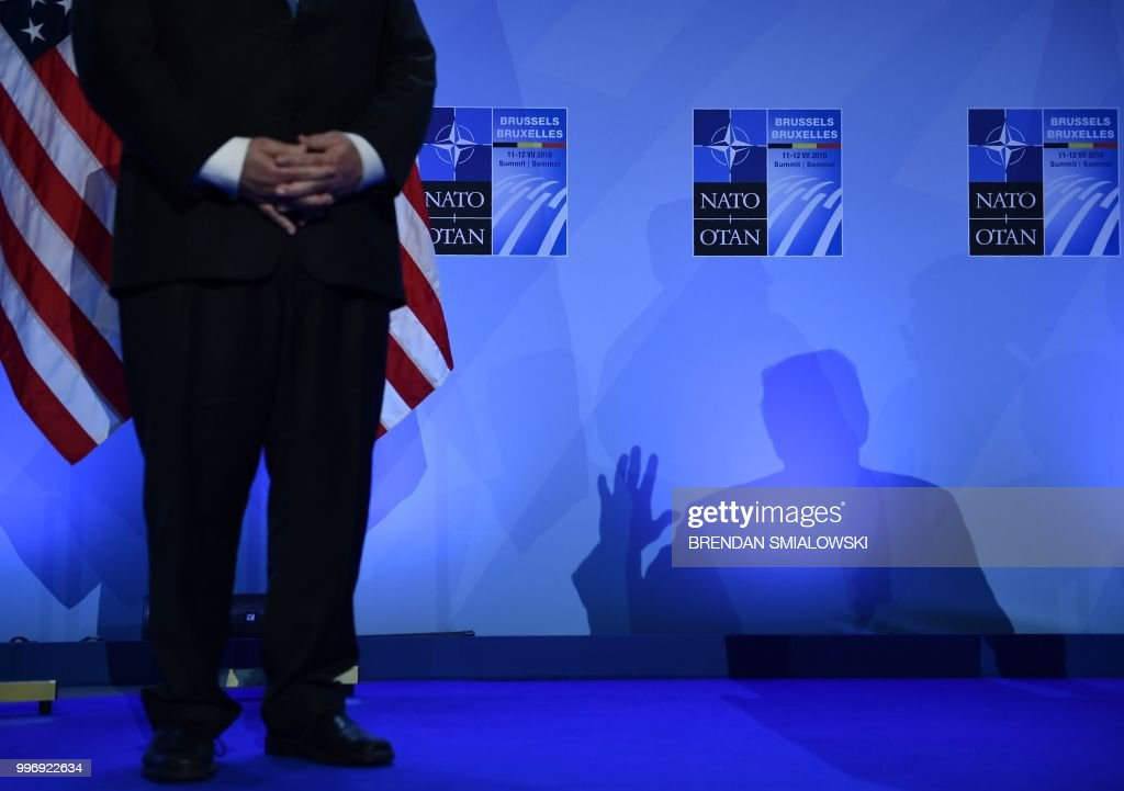 Secretary of State Mike Pompeo (L) looks on as US President Donald Trump casts a shadow as he addresses a press conference on the second day of the North Atlantic Treaty Organization (NATO) summit in Brussels on July 12, 2018.