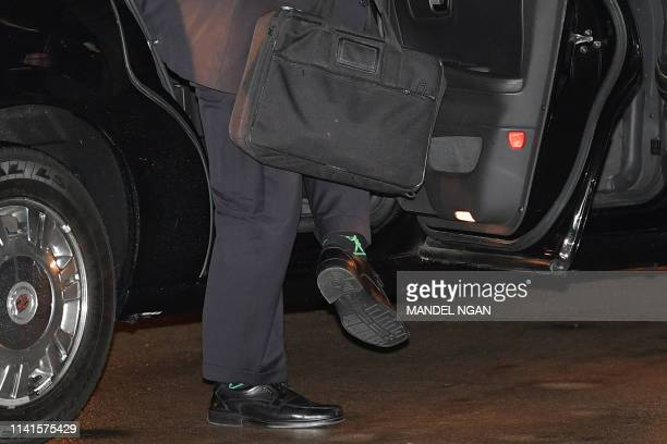 Secretary of State Mike Pompeo makes his way to board a flight from Andrews Air Force Base, as a figure of a toy soldier in his socks is seen, in...