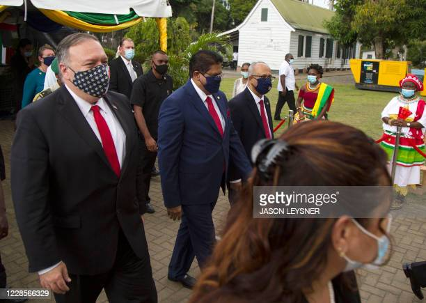 US Secretary of State Mike Pompeo walks alongside Surinam's President Chan Santokhi and Surinam's Minister of Foreign Affairs Albert Ramdin after a...