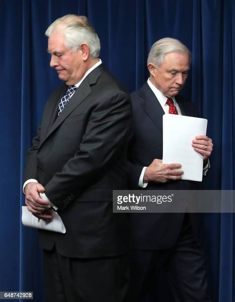 Secretary of State Rex Tillerson and Attorney General Jeff Sessions wait to give remarks related to a reconstituted travel ban at a news conference...