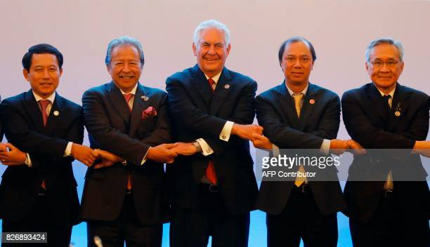 US Secretary of State Rex Tillerson links arms with Association of Southeast Asian Nations foreign ministers as they take part in the ASEANUS...